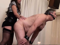 Dominatrix fucks slave with a strap on